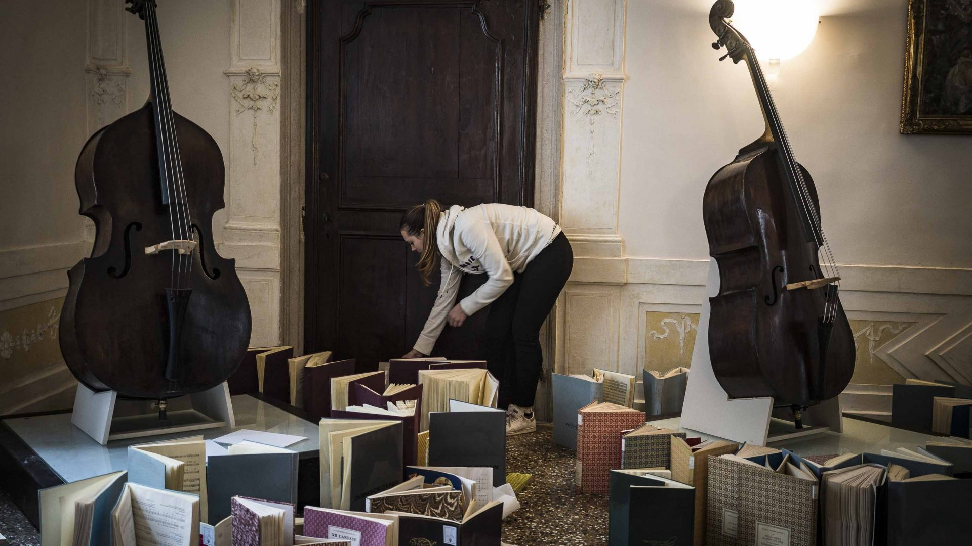 A volunteer student checks important volumes at Venice's Conservatory of Music.