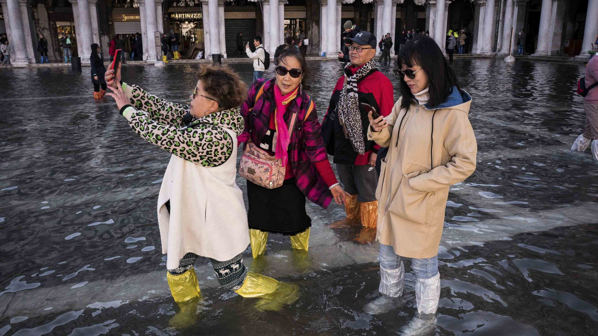 Chinese tourists taking a selfie at a flooded Piazza San Marco.