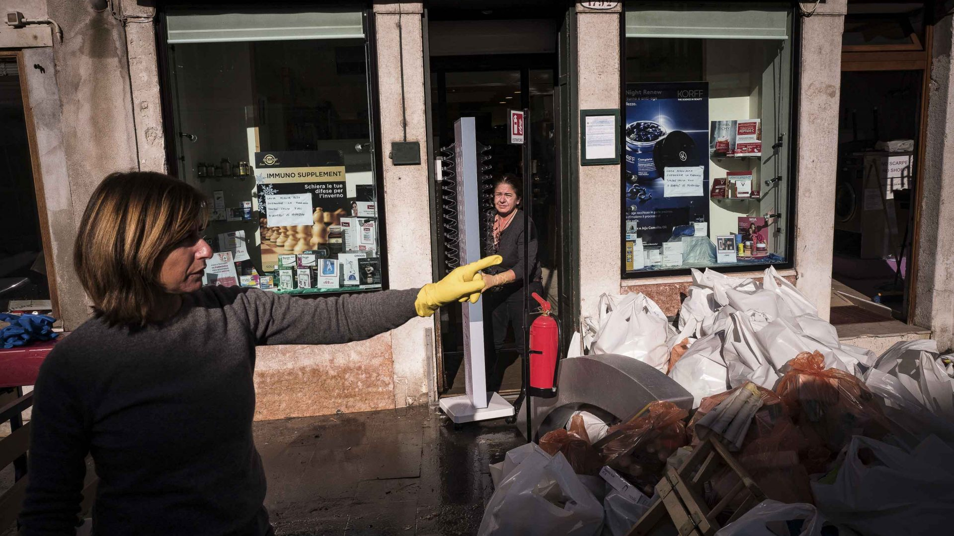 At a pharmacy on Via Garibaldi, workers are throwing away water-damaged medicines.