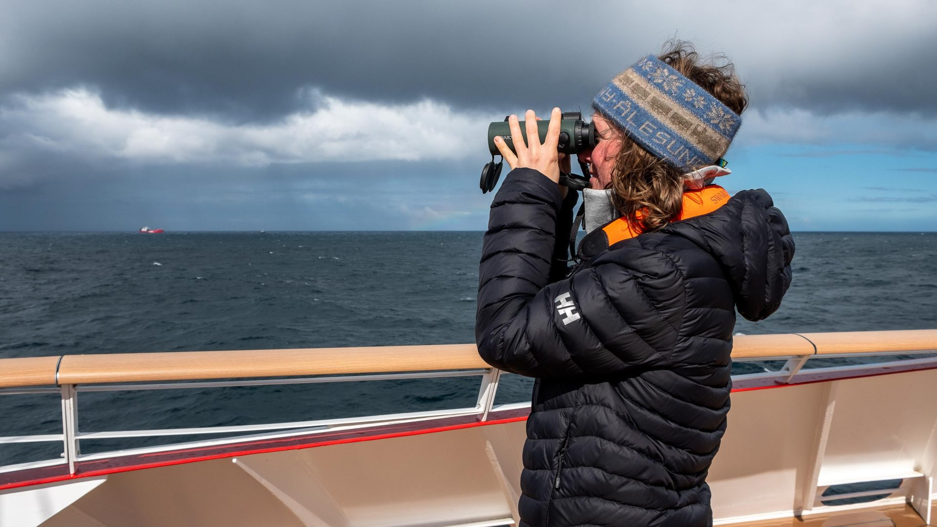 A passenger aboard the world's first hybrid cruise ship MS Roald Amundsen uses binoculars to look out at the views.