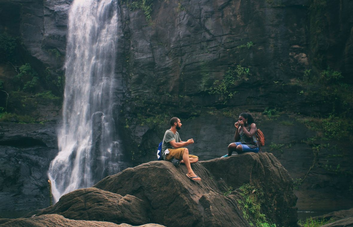 Friends sit by a waterfall in Pariyaram, India.