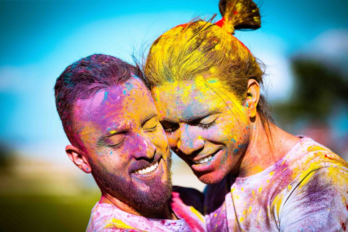 Two men covered in colored paints embrace in Brasilia, Brazil.