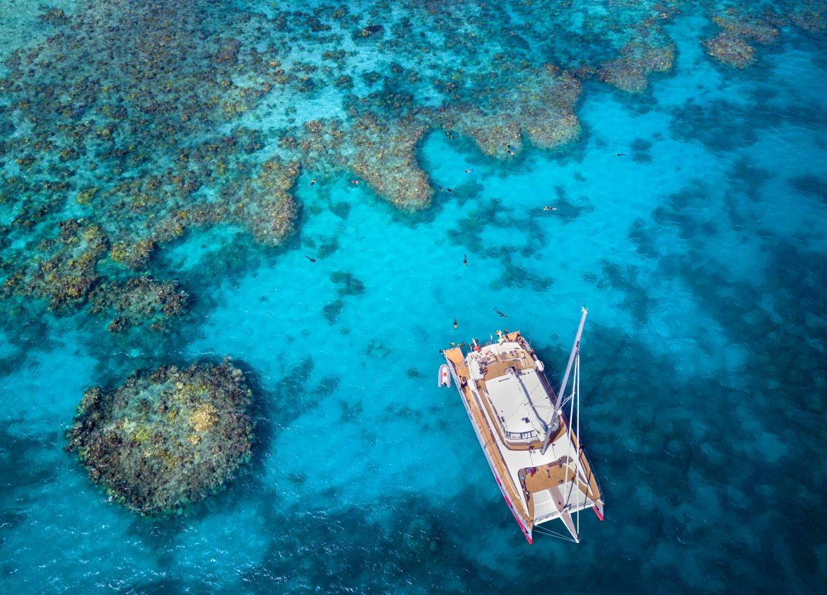 An aerial shot of a tourist boat at the Great Barrier Reef.