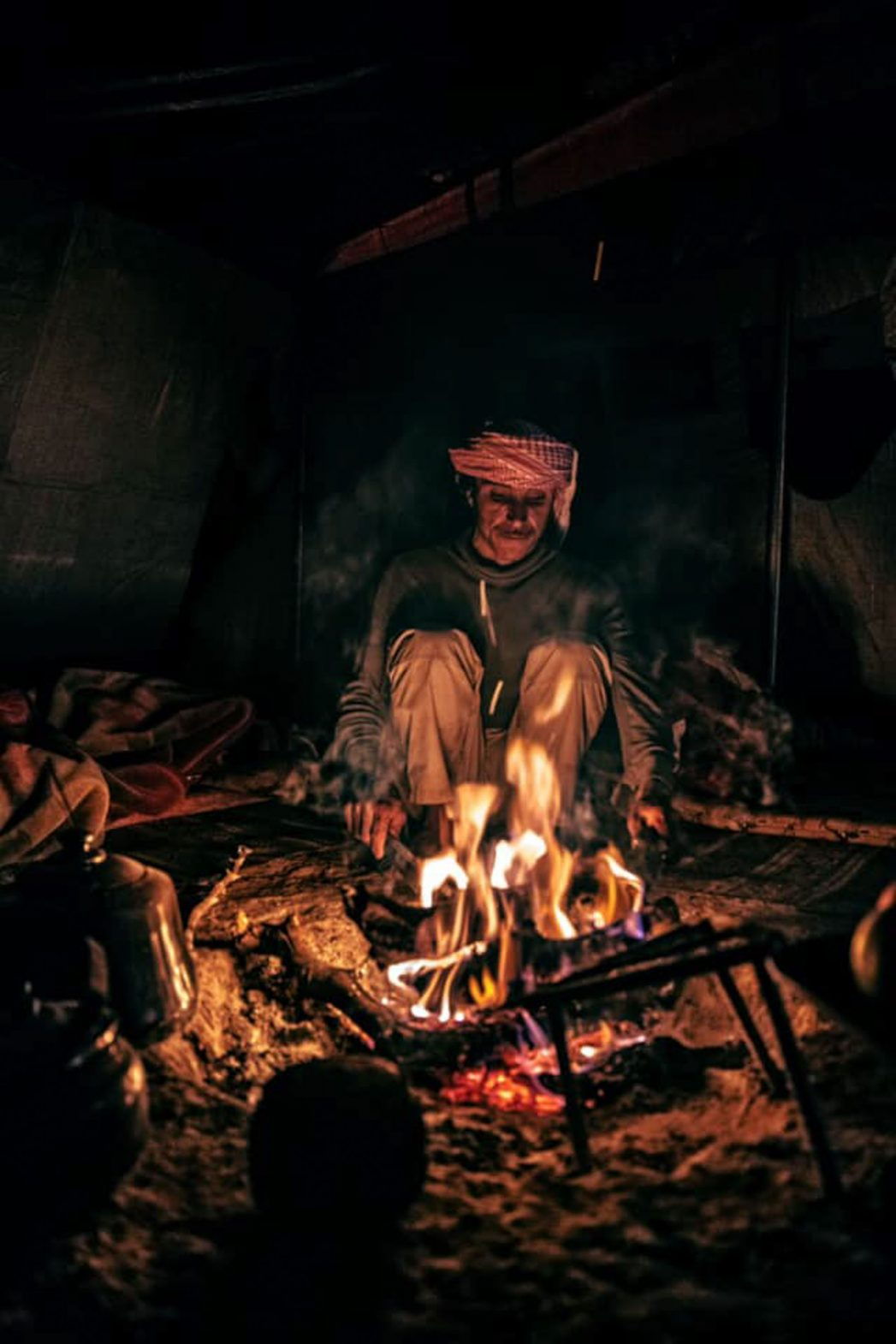 A Bedouin lights the fire while camping in Petra.