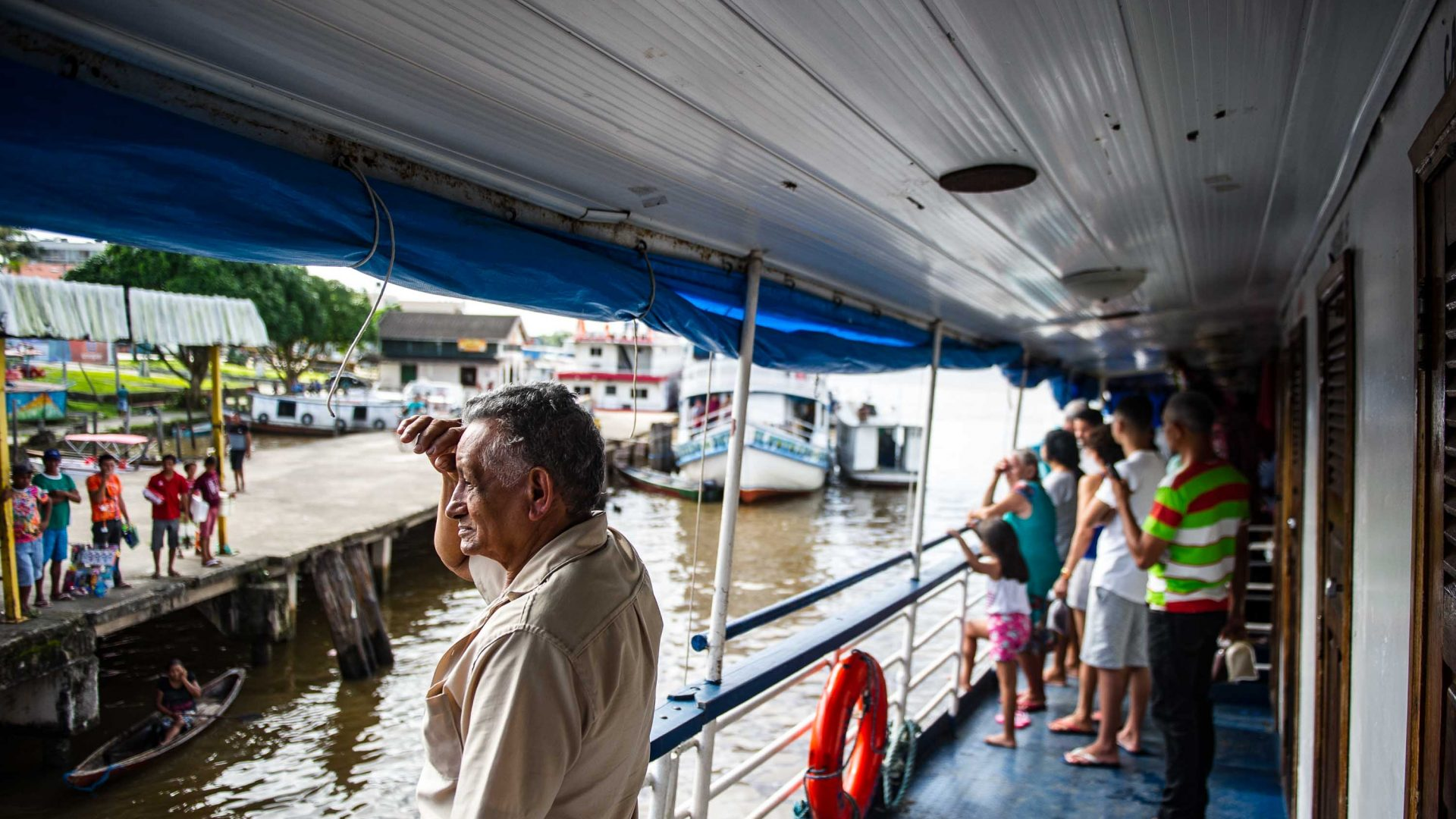 A passenger looks out as the Cisne Branco riverboat arrives at a port.