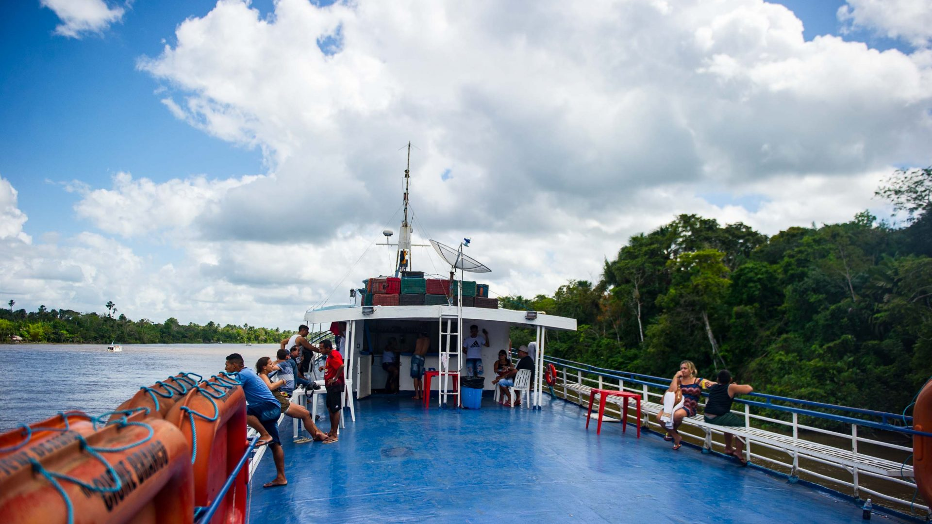 Passengers relax on the deck of Cisne Branco riverboat.