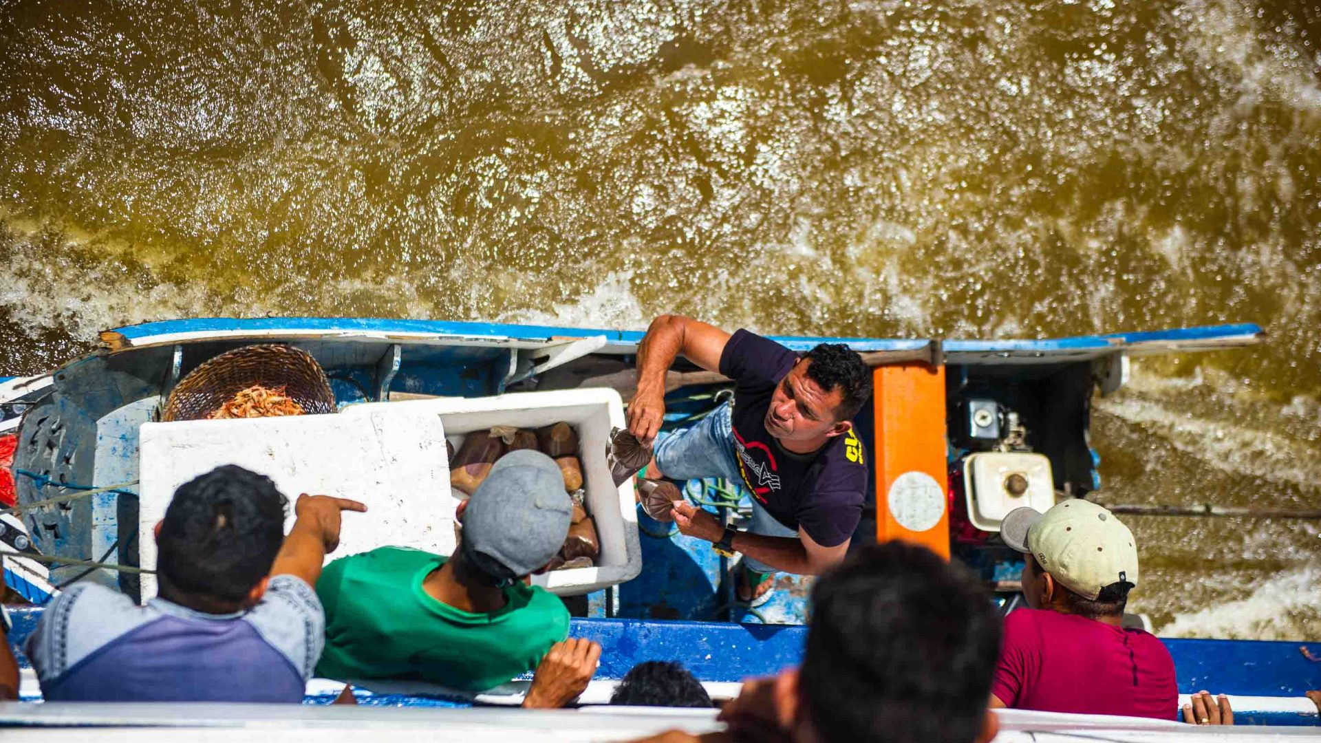 An acai berry vendor reaches up to passengers on the Cisne Branco riverboat.