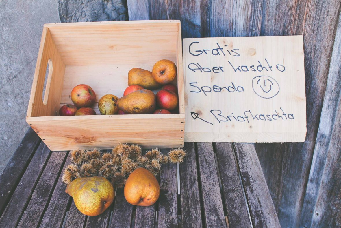 The writer and fellow hikers snack on pears from a wooden box of free fruit set out for passers-by.