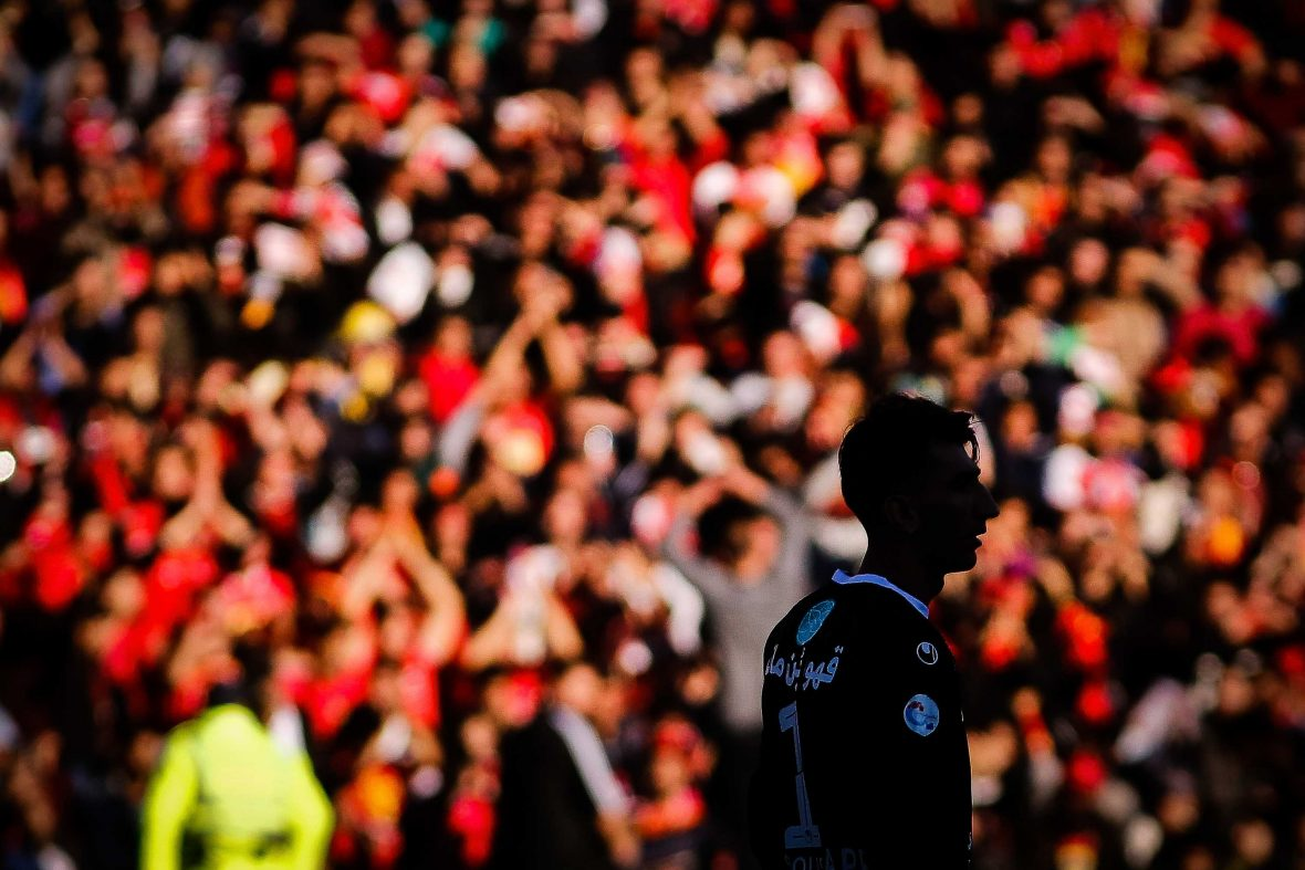 A player is silhouetted against a sea of Persepolis fans at the Tehran Derby.