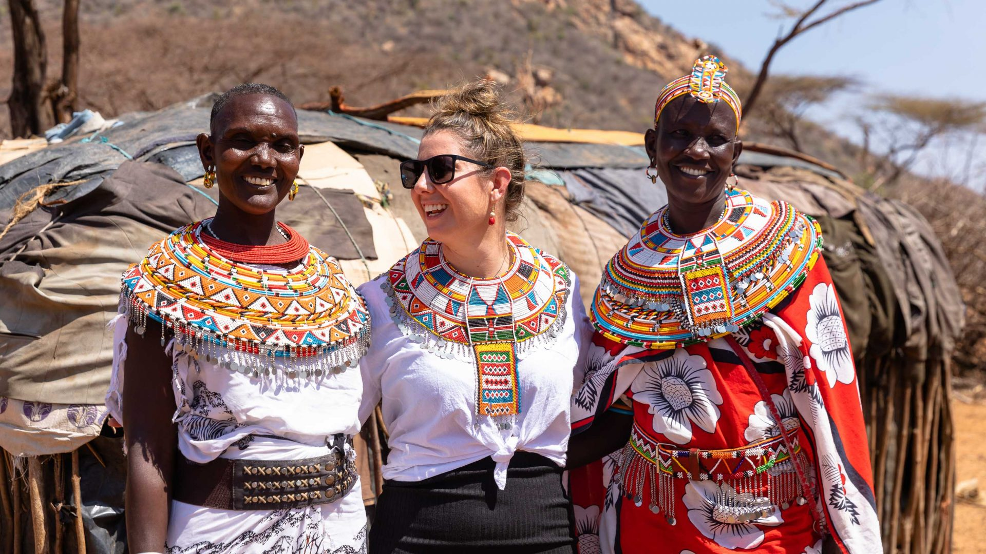 A traveler on Intrepid Travel's women's-only expedition engages with other women in an Umoja village in Samburu National Park.