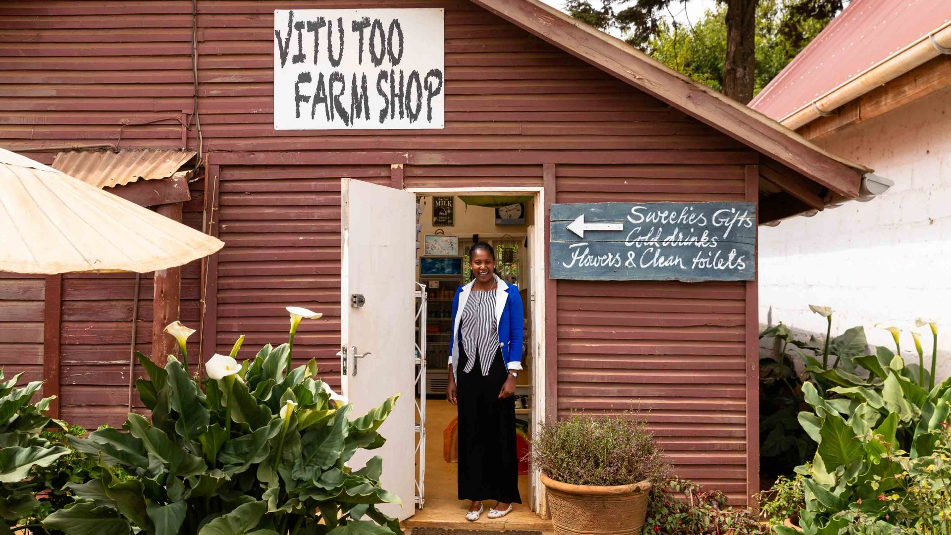 A woman stands outside Vitu Too farm shop, visited during Intrepid Travel's women's-only expedition to Kenya.