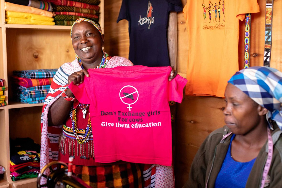 Hellen holds up a T-shirt with the motto 'Don't exchange girls for cows, give them an education' in the Maasai Tepesua village.