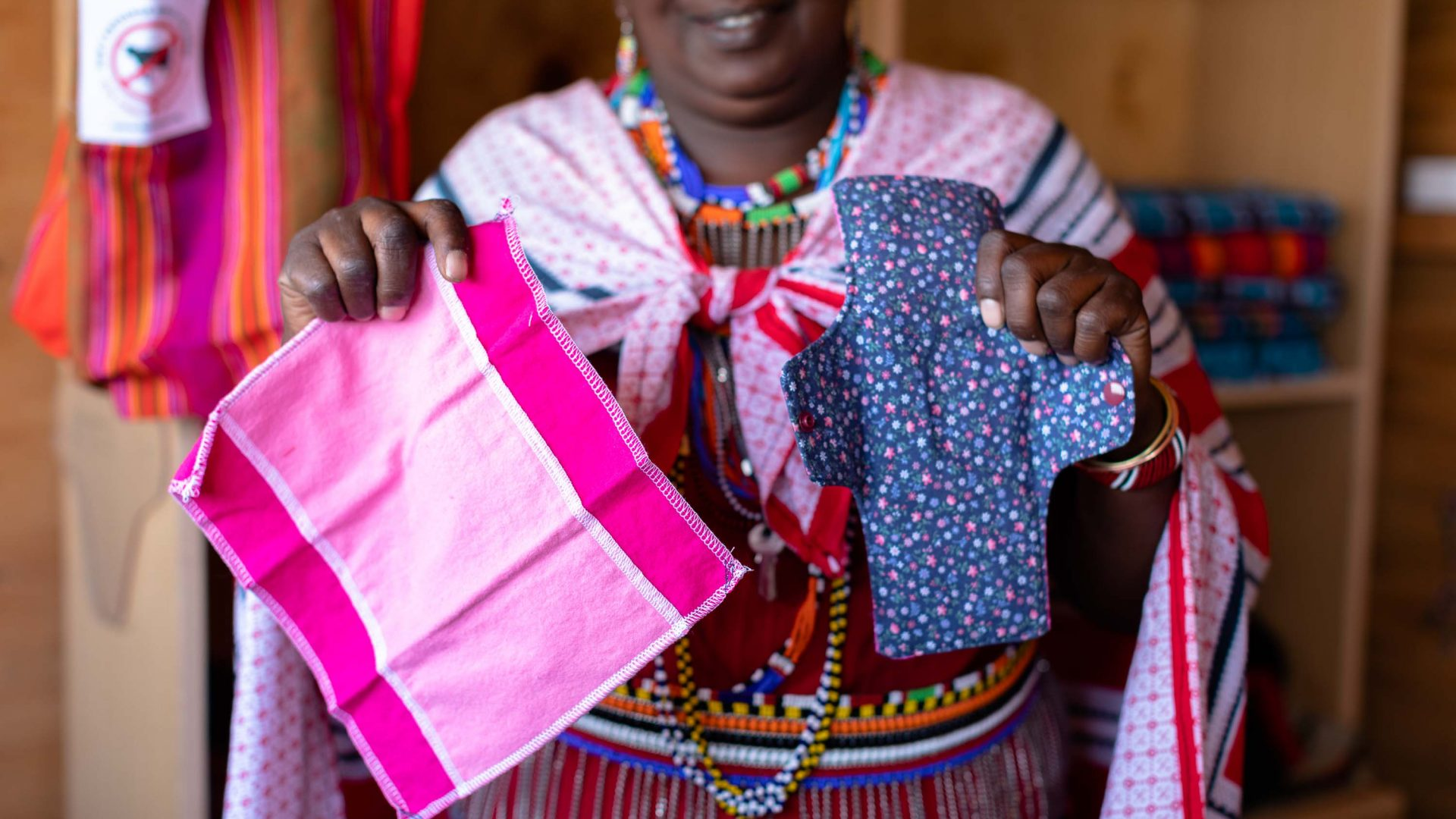 A woman shows off the women's sanitary items she's making for sale in the Maasai Tepesua Village.