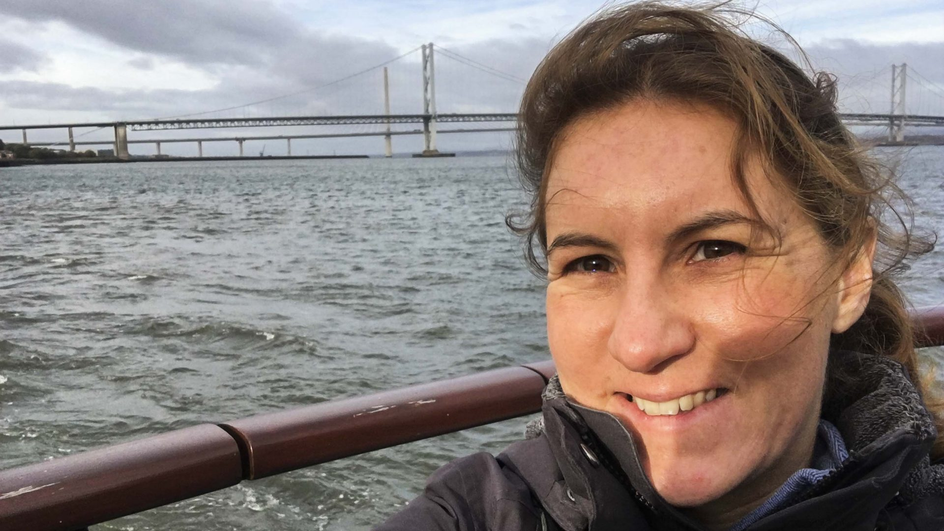 Helen Ochyra on a boat trip in the Forth against the backdrop of the Forth Road Bridge and the Queensferry Crossing.