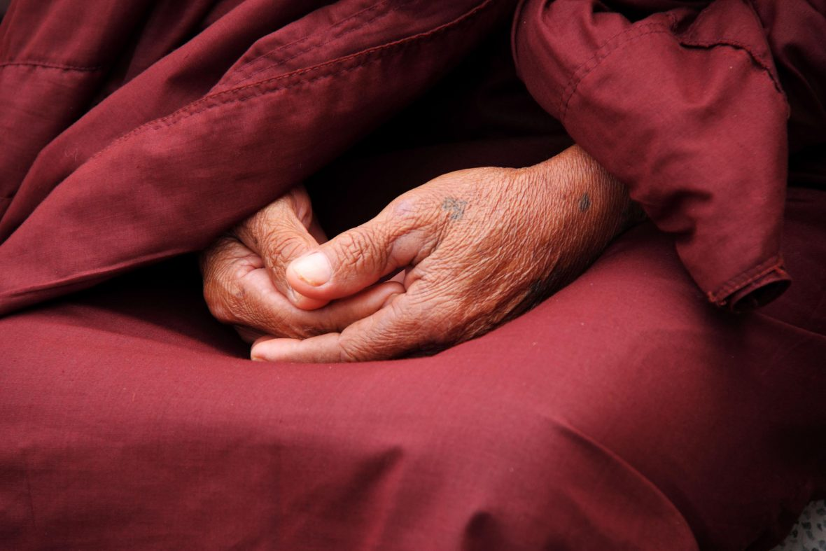 A monk crosses his hands in meditation.