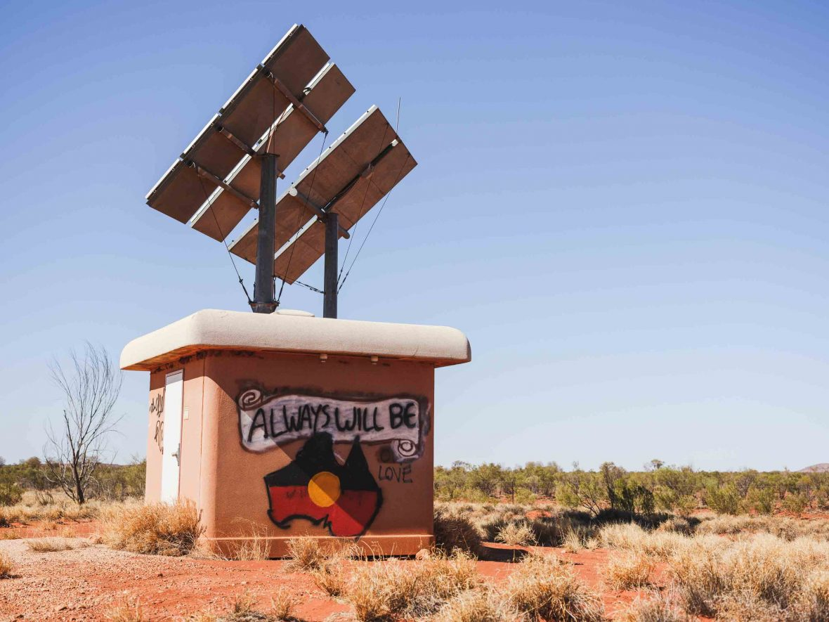 """Graffiti in the Australian outback that reads """"Always will be' with a picture of Australia with the Aboriginal flag."""