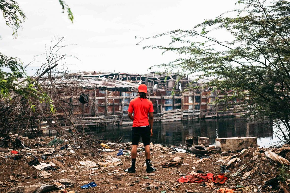 A man with his back turned stands among rubbish as he looks out over dilapidated houses.