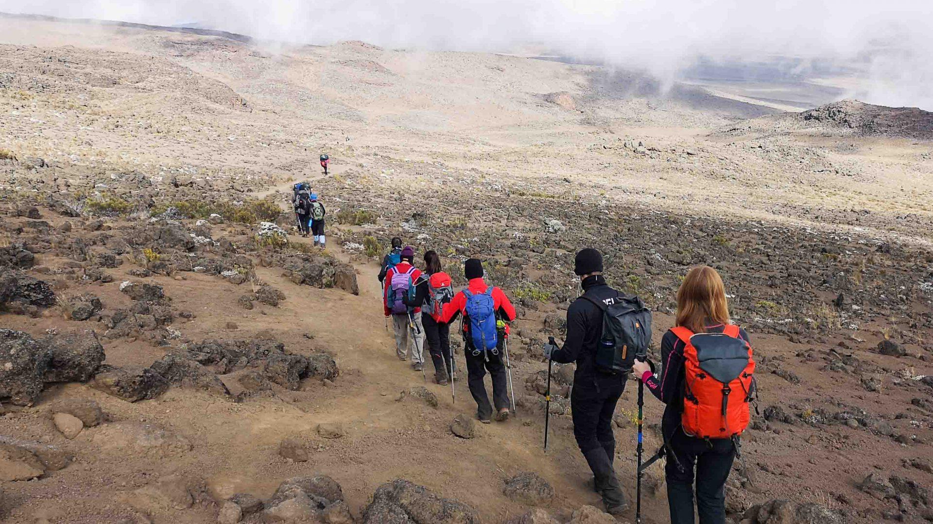 Hikers walking up an arid, barren part of the mountain.