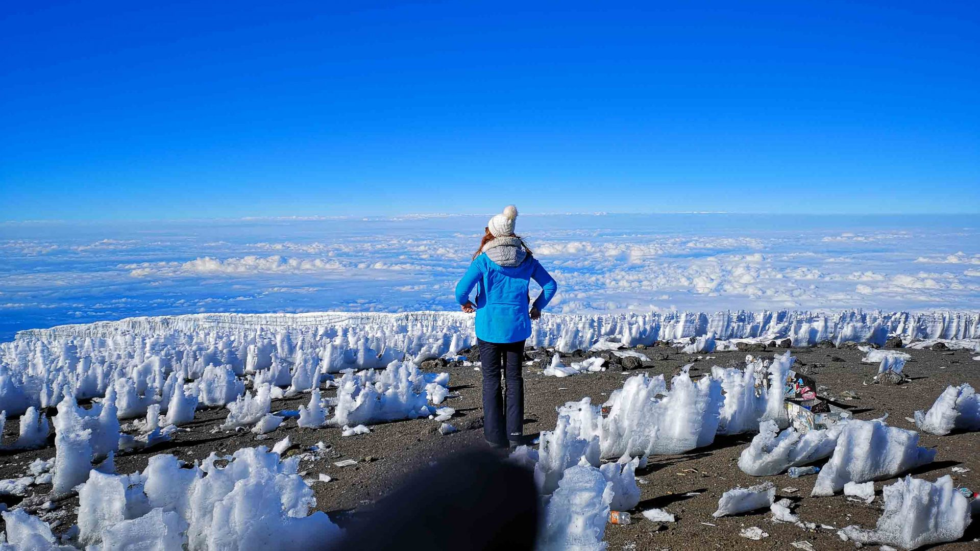 The writer stands back to camera looking out at the view, surrounded by snow.