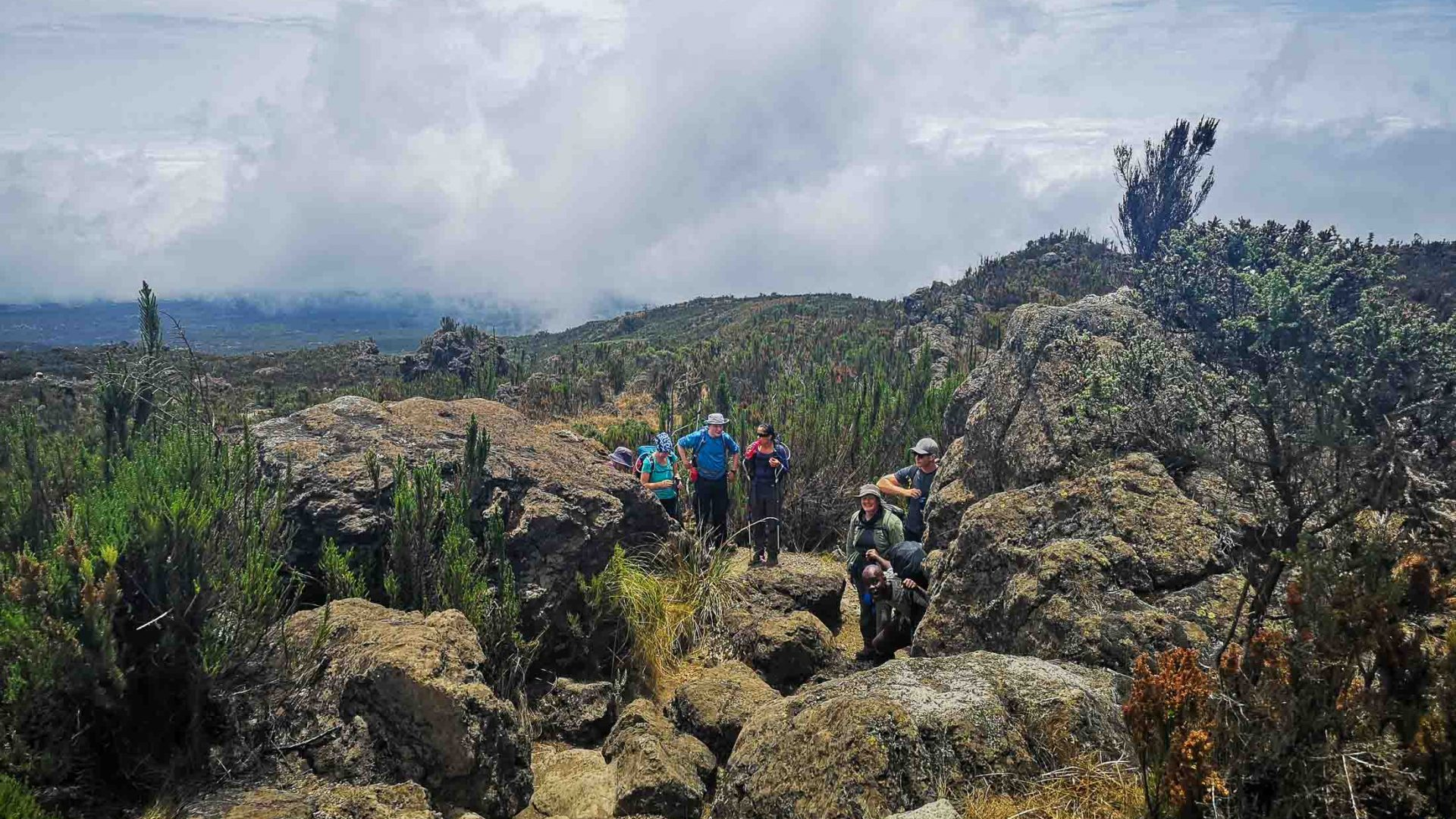 Hikers clamber through rocks along the Rongai Route to Kilimanjaro.
