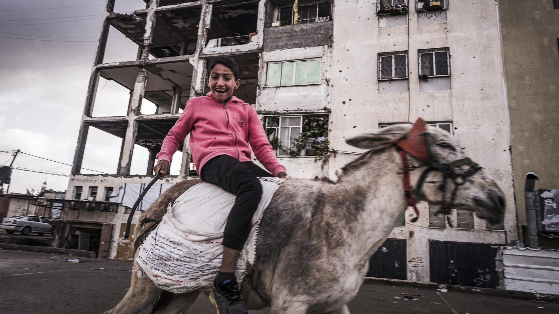 A young boy rides his donkey past several partially destroyed buildings in Gaza.