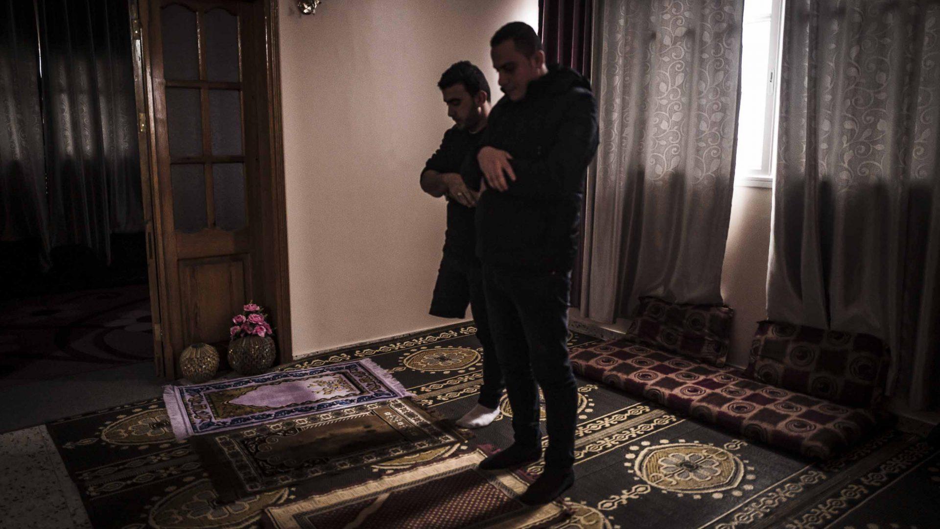 Two men pray at home in Gaza.