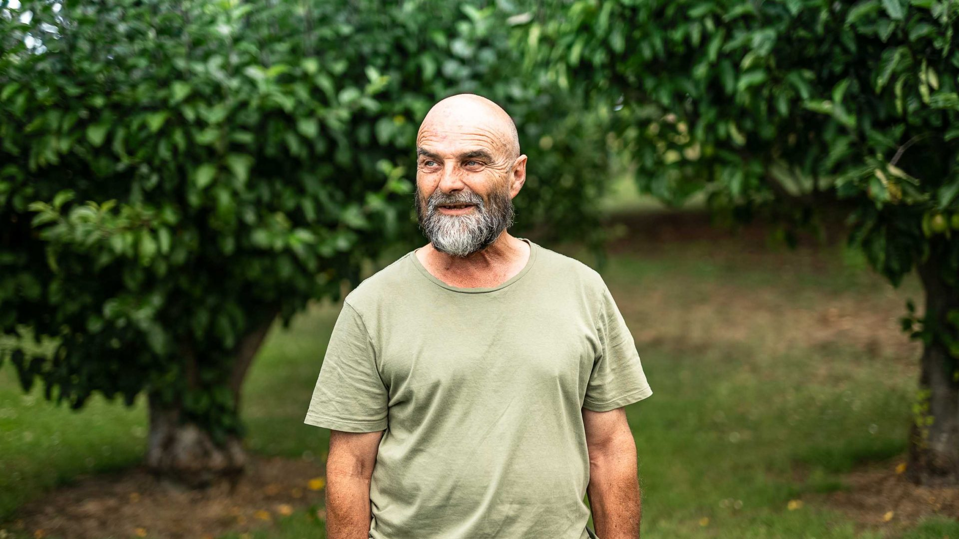 Martin smiles in front of trees.