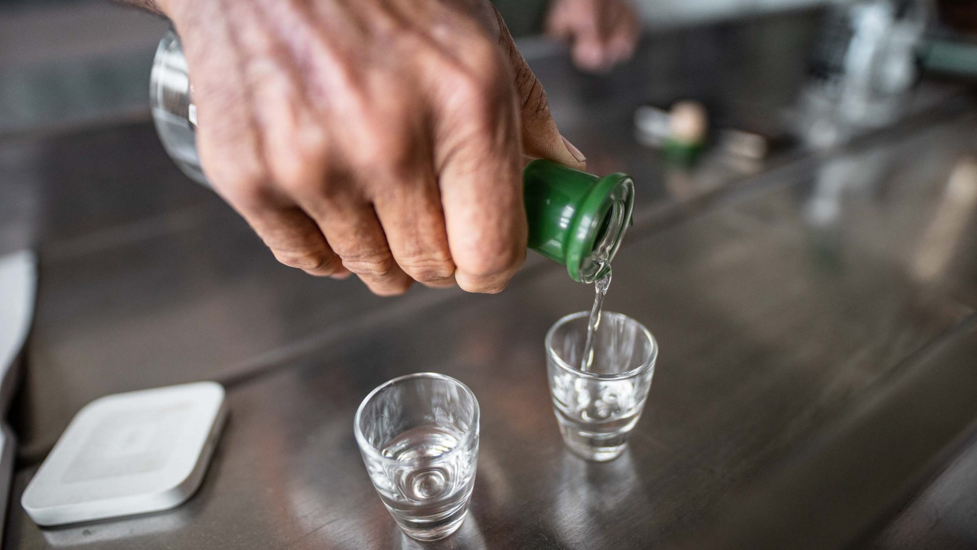 A hand pours a shot of alcohol