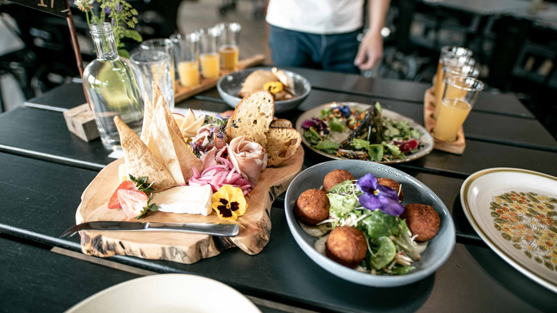 A feast of fresh food and drinks on a wooden table.