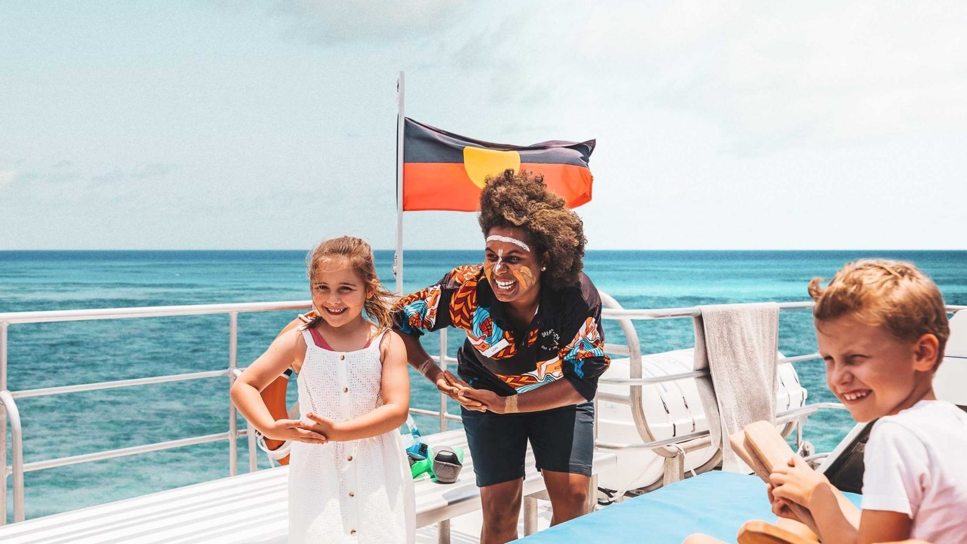 A woman and child on a boat with an Aboriginal flag.