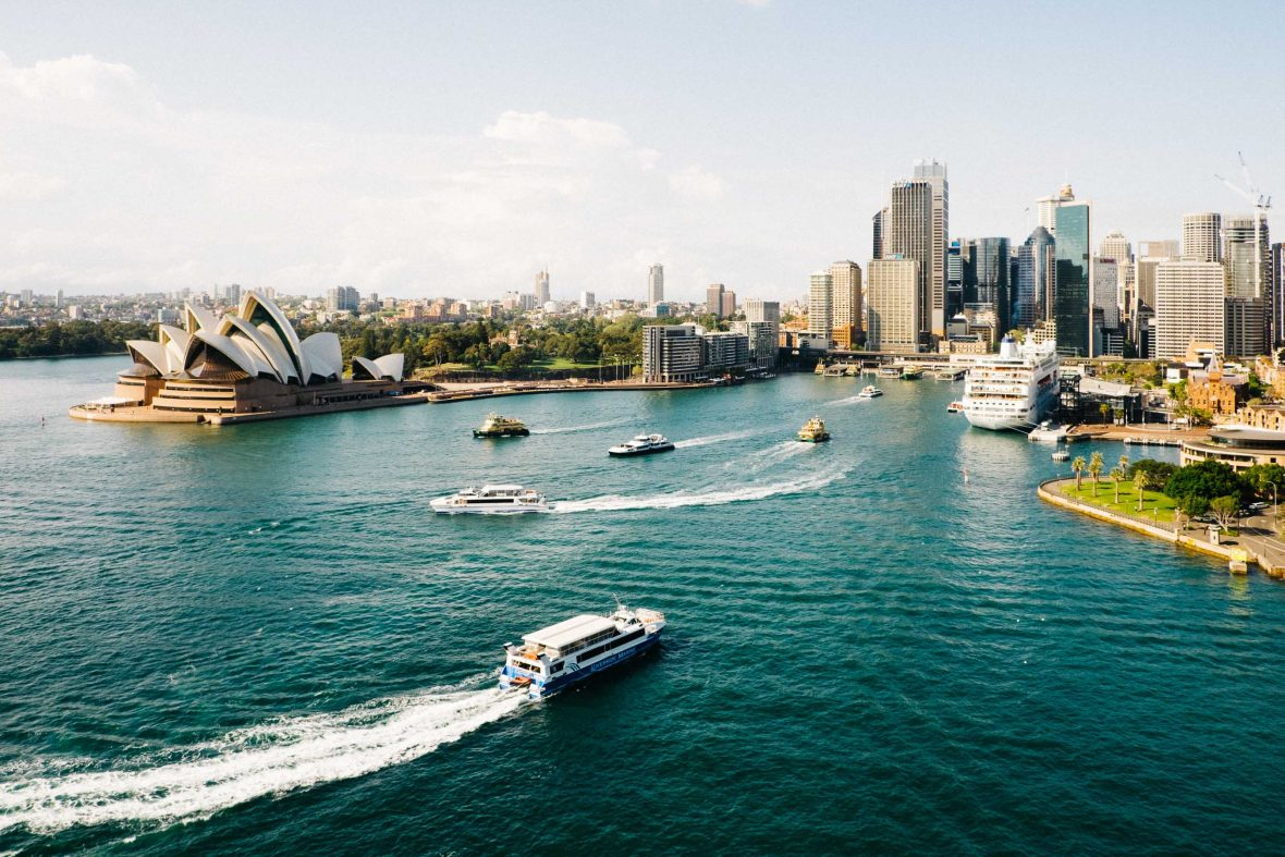 Boats, the Opera House and buildings line Sydney Harbor