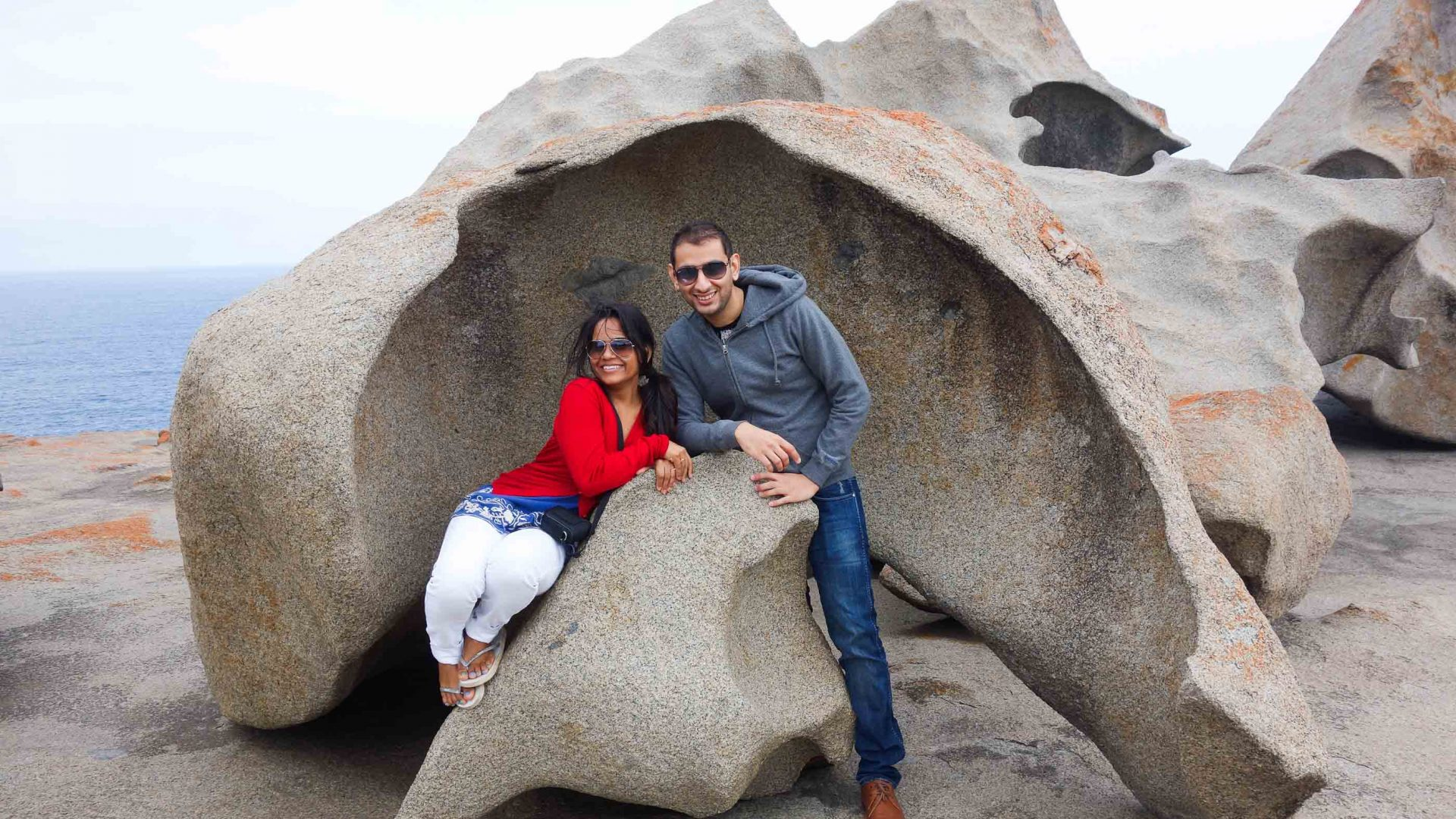 A couple pose in front of a big rock.
