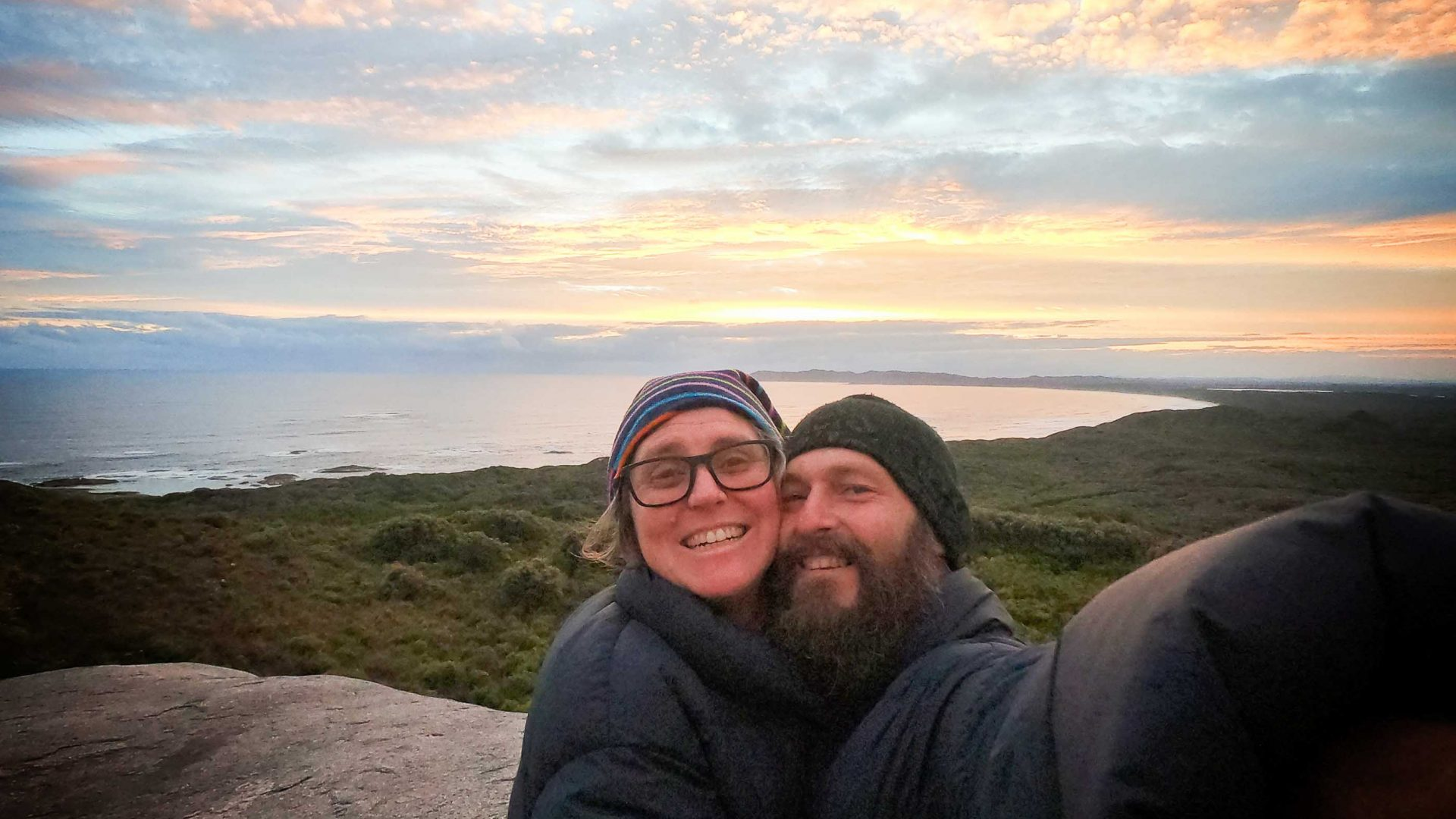A couple do a selfie in front of a view of water, trees and sunset.