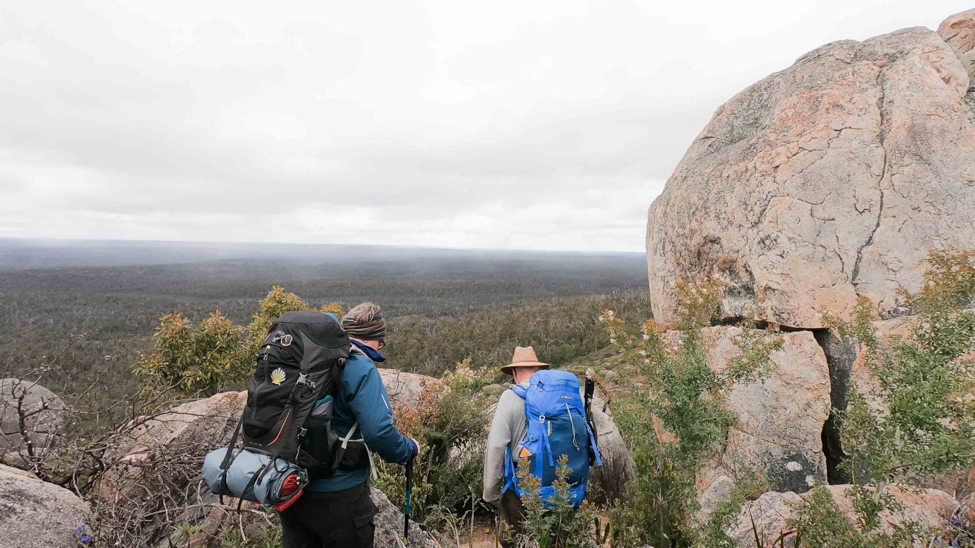 Two people hiking through boulders.