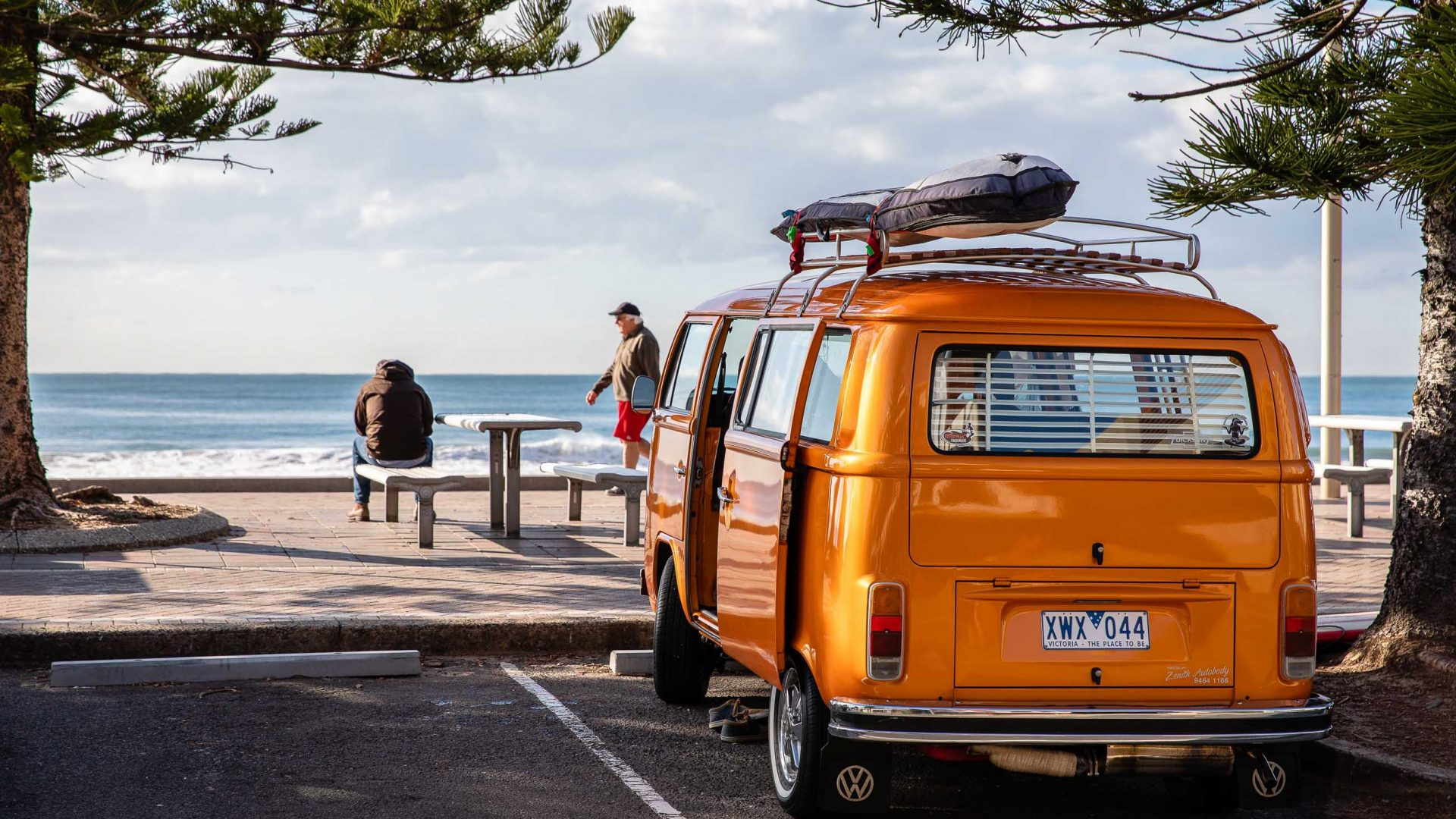 A yellow combi van is parked at the beach.