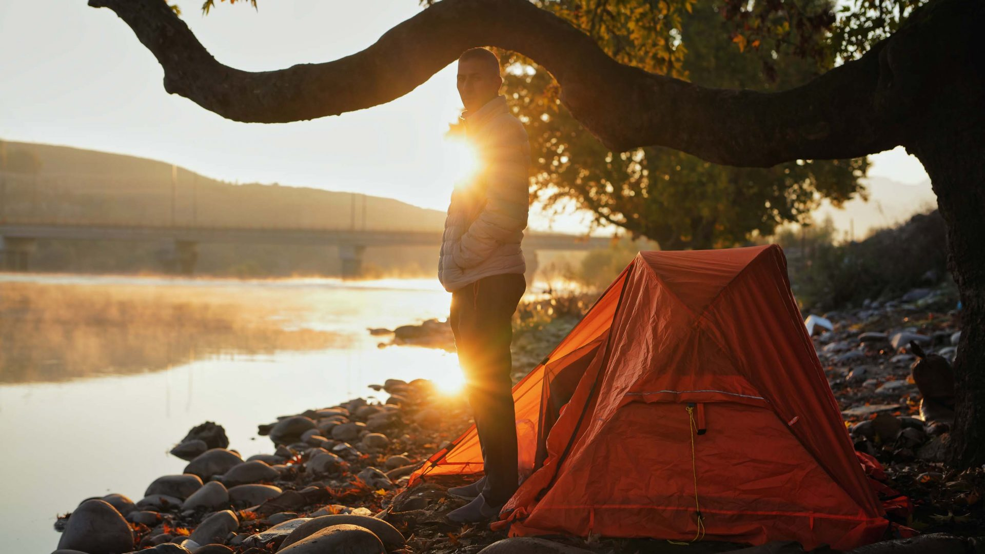 A man stands in the morning light alongside his tent, near a river.