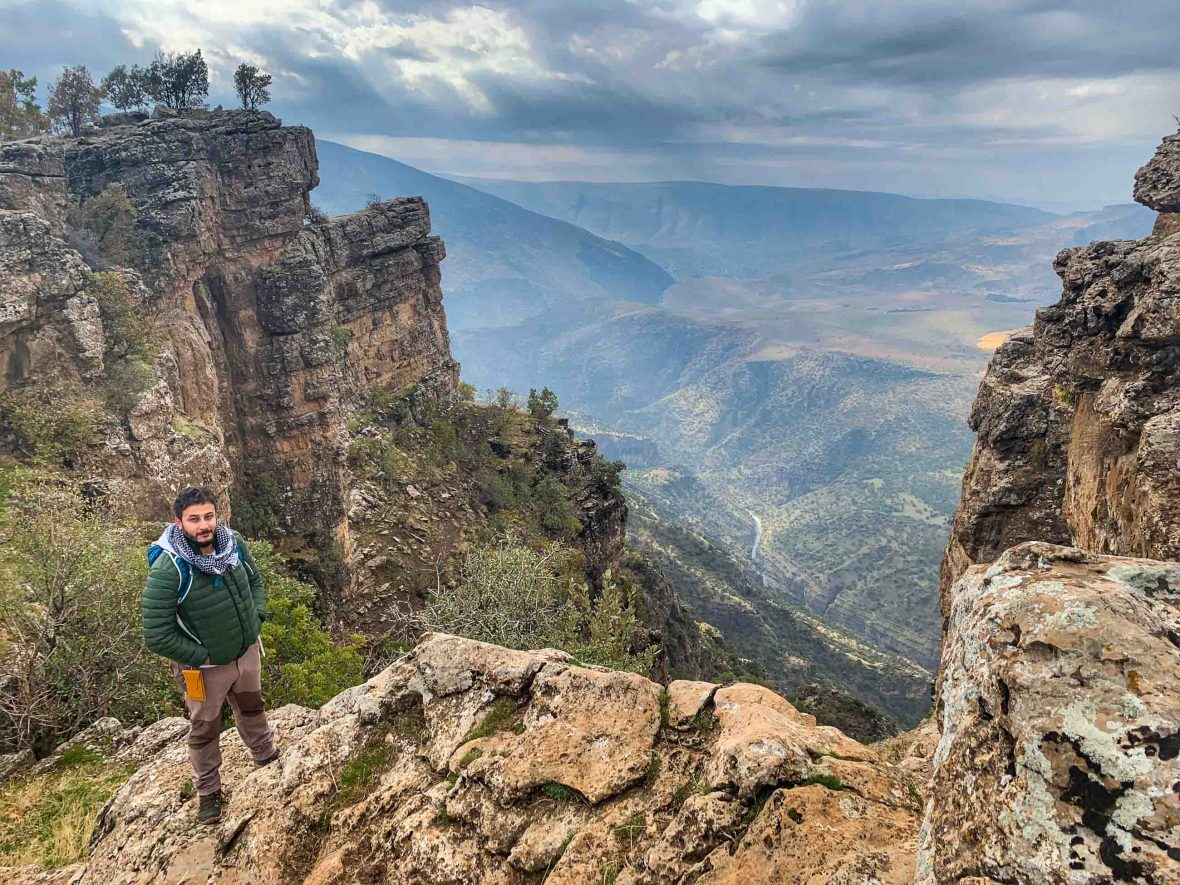 A man, Laween, standing near the edge of a rocky valley viewpoint.