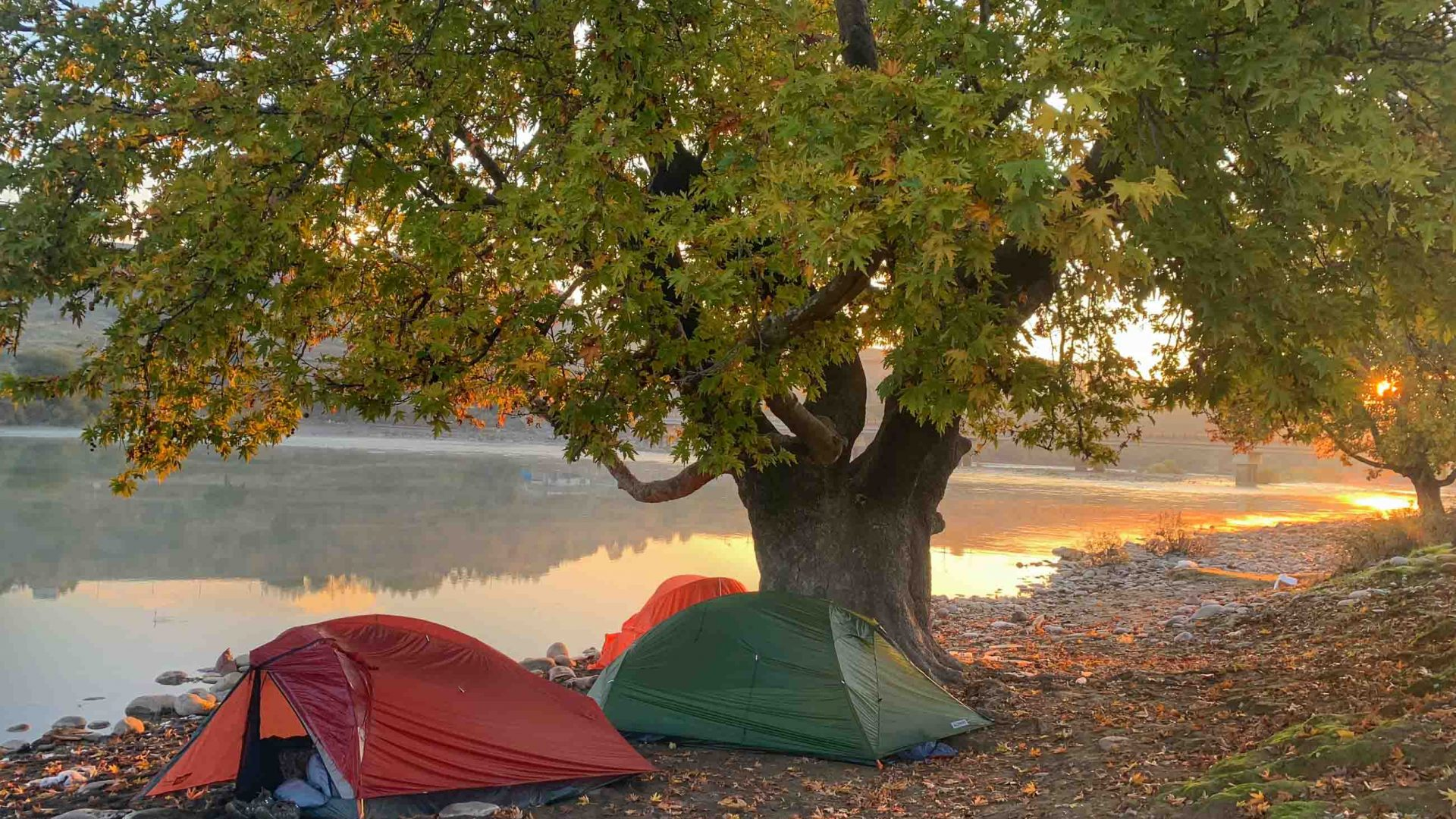 Two tents alongside a river at sunset.