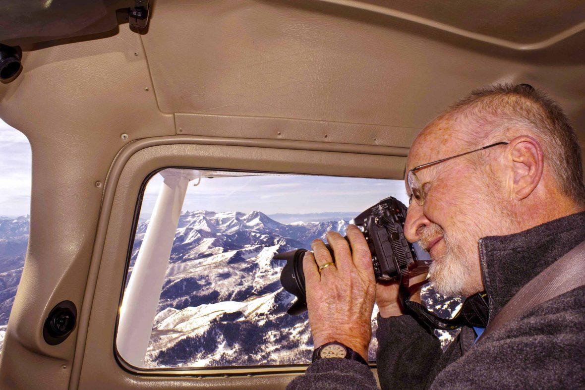 James takes photos of mountains through the window of a small plane.