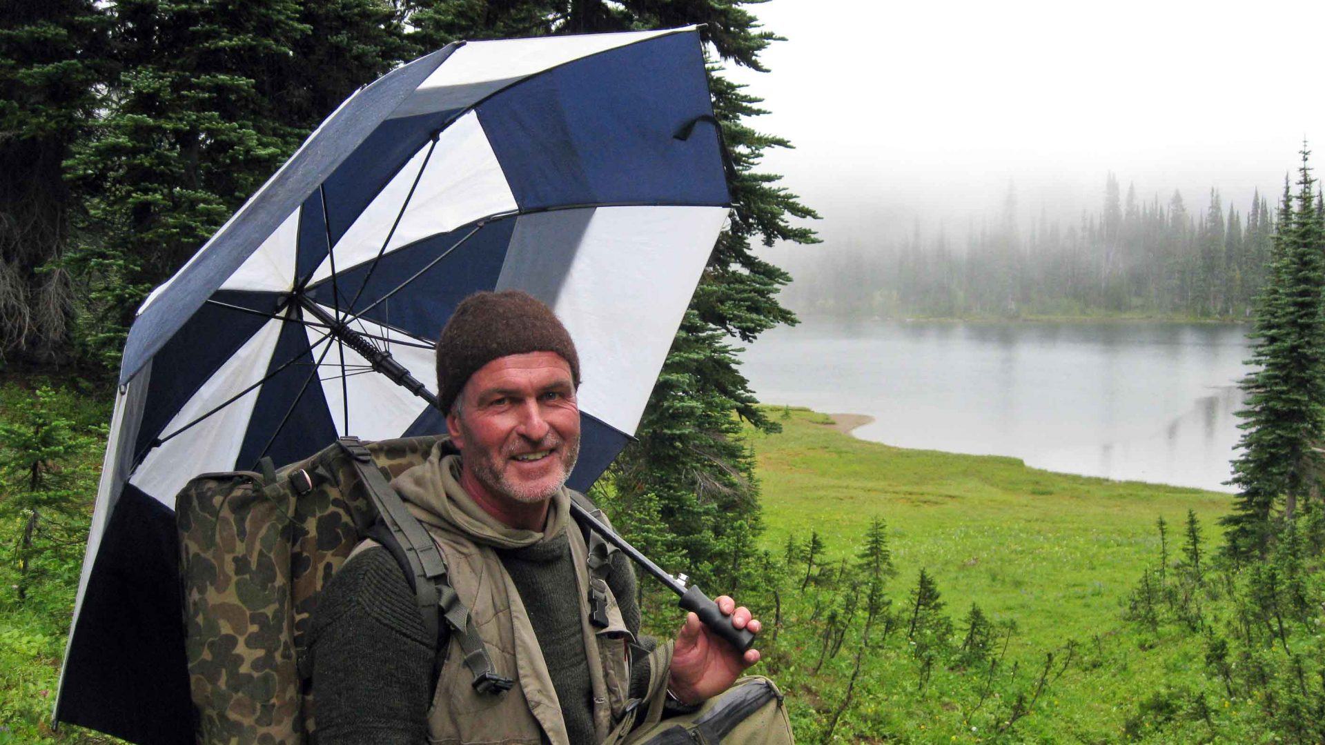 Gordon stands with an umbrella near green grass and grey river.