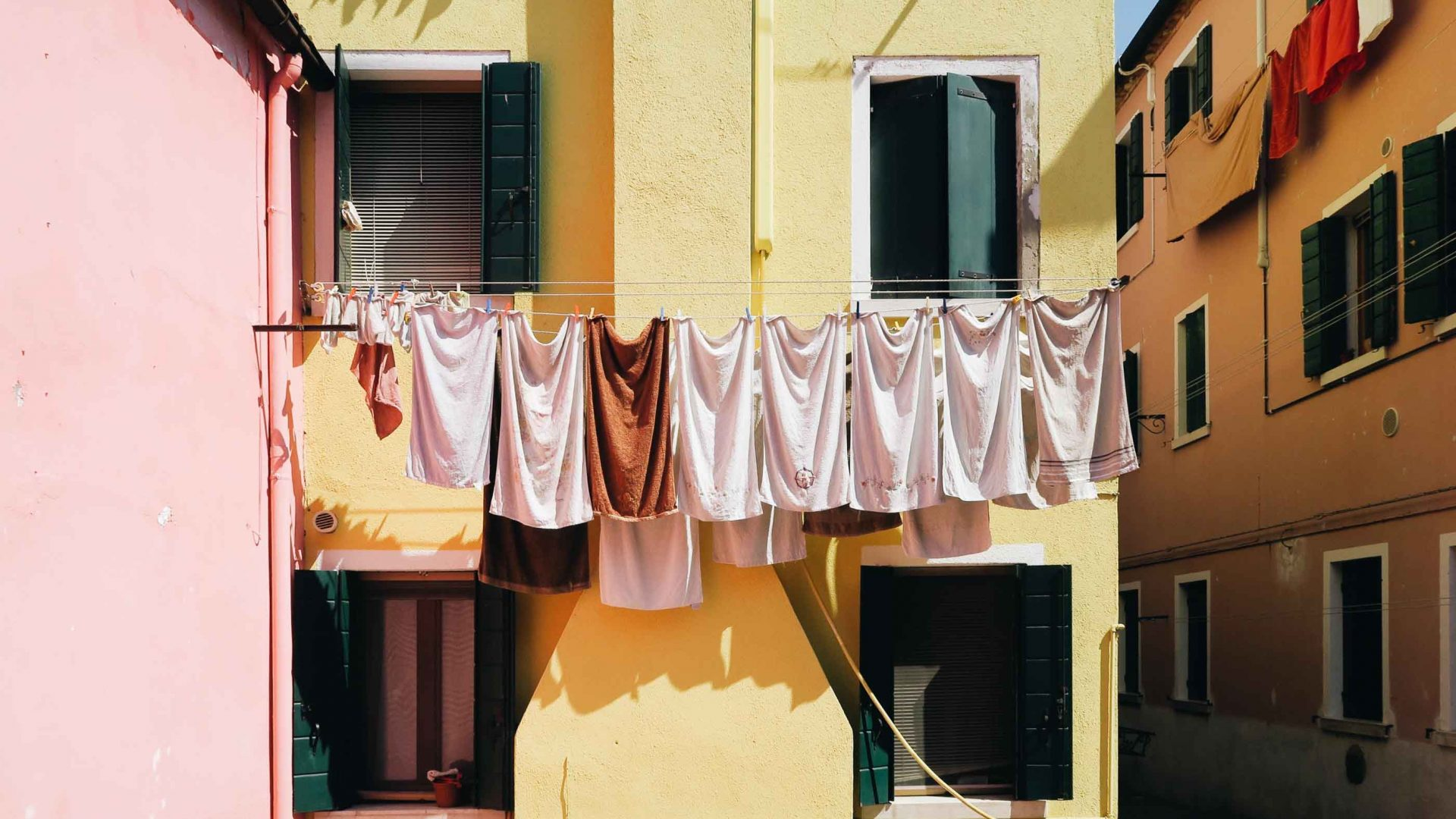Laundry hanging from a line in front of a yellow building.