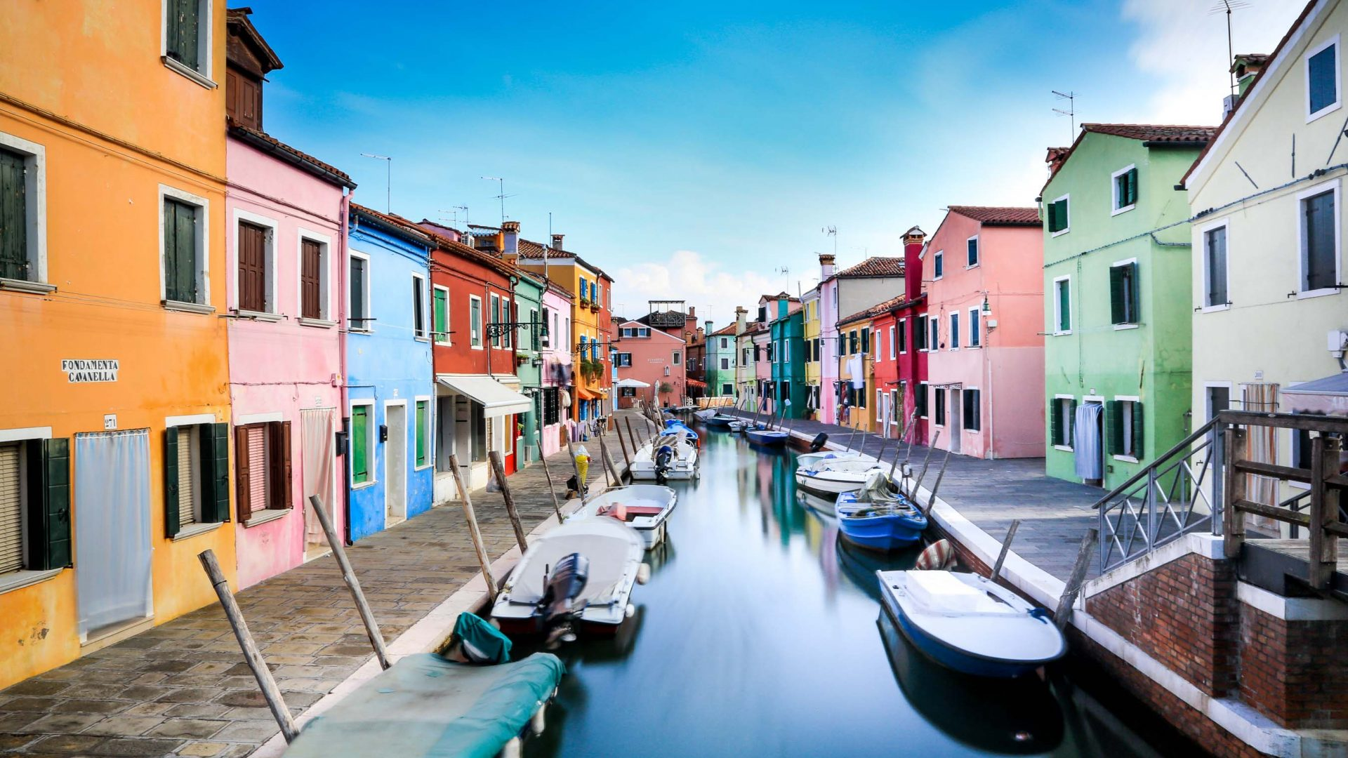 Colorful houses and boats in a canal in Burano.