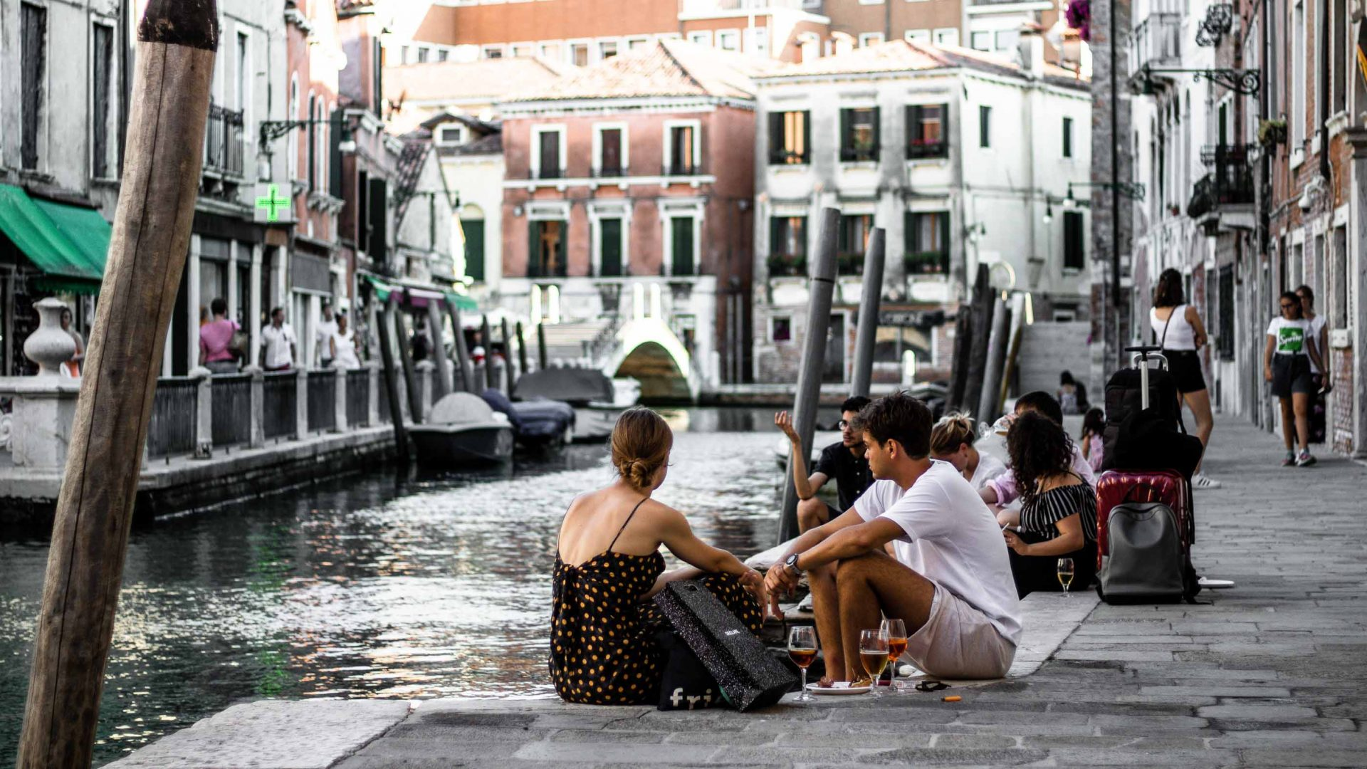 Tourists sit alongside one of the canals in Venice.