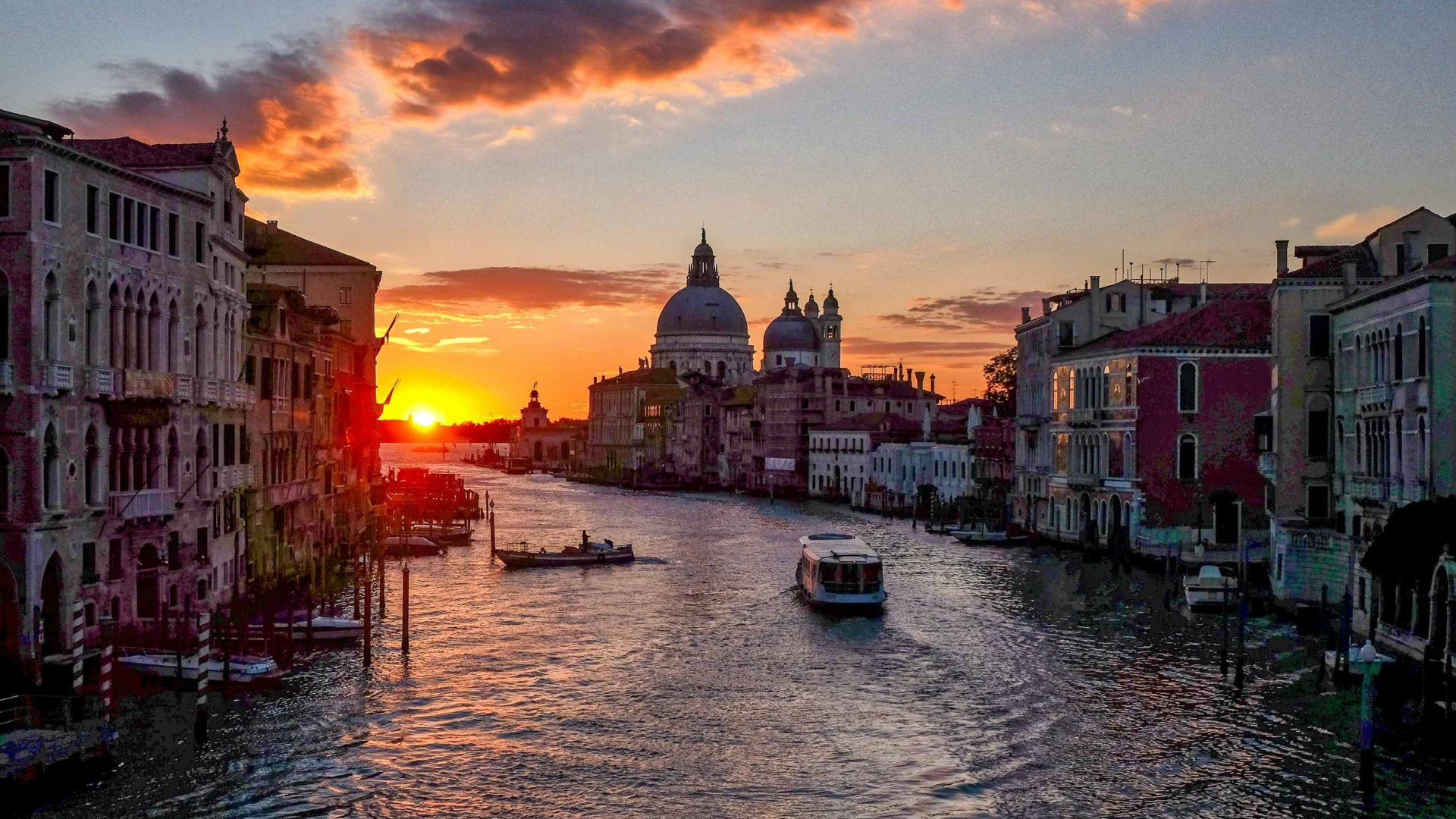 The sun sets over the canal and buildings of Venice.