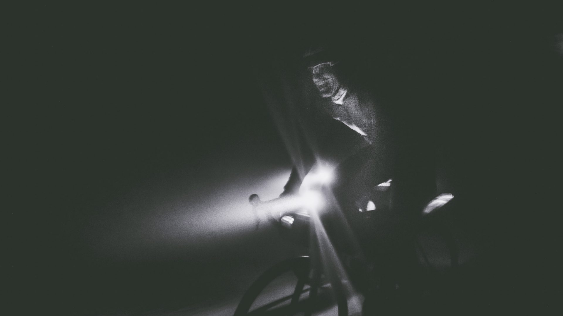A bike rider can just be seen in the darkness.