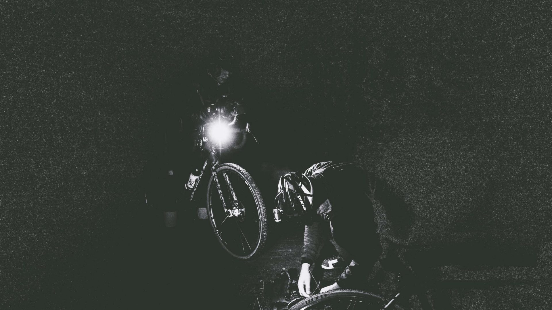 Two riders are barely visible in the dark.