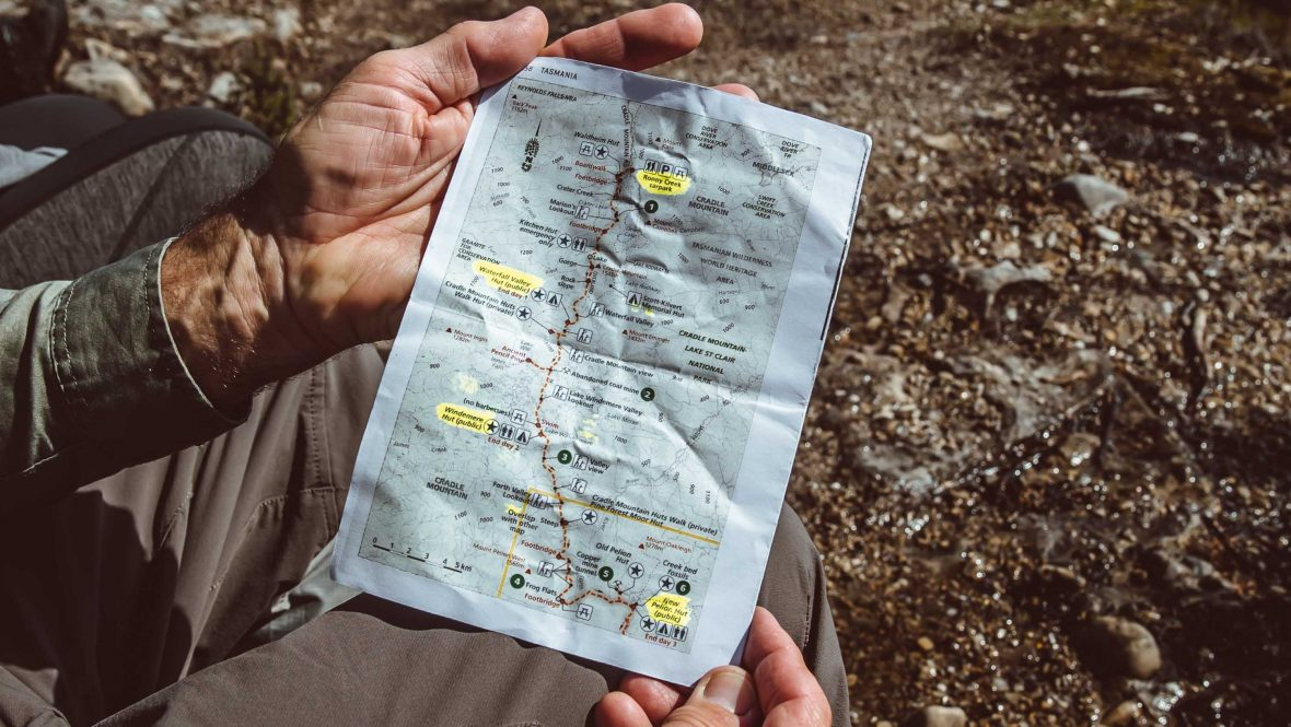 Hands hold a map of the Overland Track.