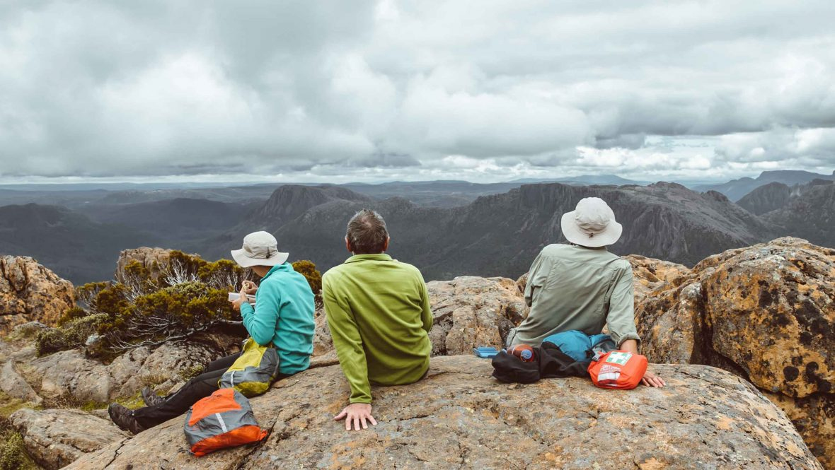 Three travellers look out at the view on the Overland Track.