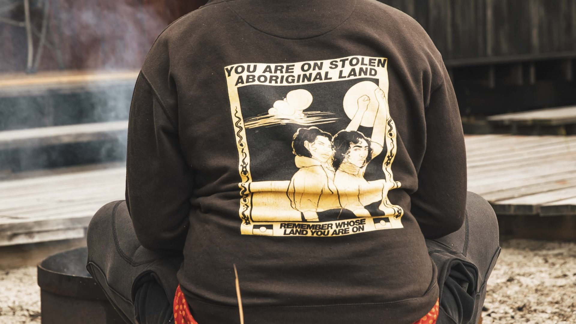 The back of someone's jumper reads 'You are on stolen Aboriginal land'.