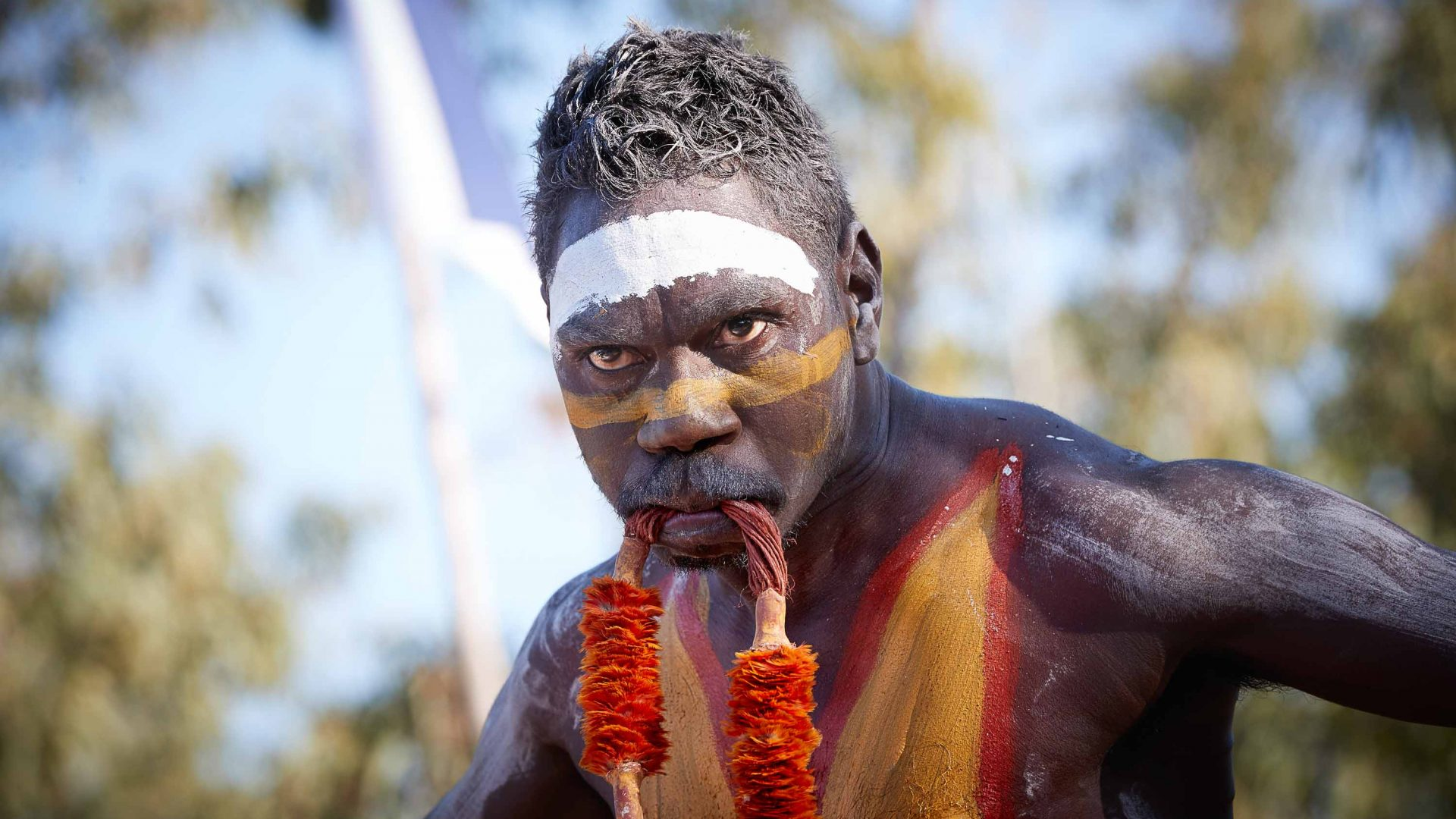 A man with face paint has an orange adornment in his mouth.